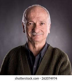 Smiling elderly man on a dark background