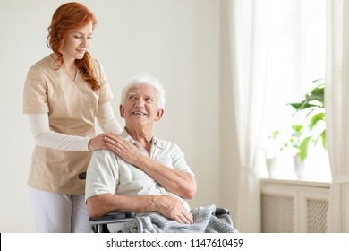 Smiling elderly man in a wheelchair and friendly caregiver in a nursing house