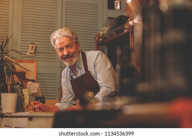 Smiling elderly man in the workshop