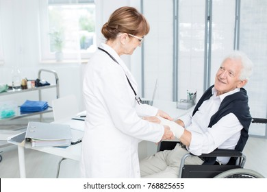 Smiling elderly patient grateful for help of a doctor in white uniform fixing his hand