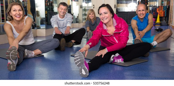 smiling elderly people doing exercise on mat in modern gym