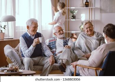 Smiling elderly people talking together in nursing home