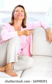 Smiling elderly senior woman with a mp3 player at home
