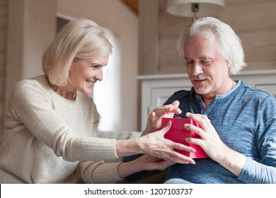 Smiling elderly wife making birthday surprise for beloved husband, aged man get present from loving spouse on special occasion, caring senior couple exchange gifts celebrating marriage anniversary