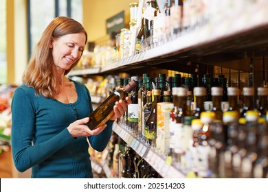 Smiling elderly woman buying a bottle of olive oil in a supermarket