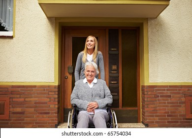 Smiling elderly woman in front of a retirement home