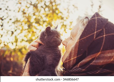 Smiling elderly woman holding little kitten on a sunset background.Smiling grandmother relaxing in garden holding a little black kitten against a sunset background.Happiness.