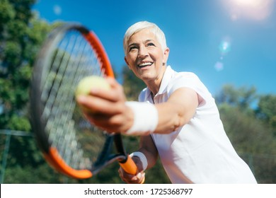 Smiling Elderly Woman Playing Tennis as a Recreational Activity - Shutterstock ID 1725368797