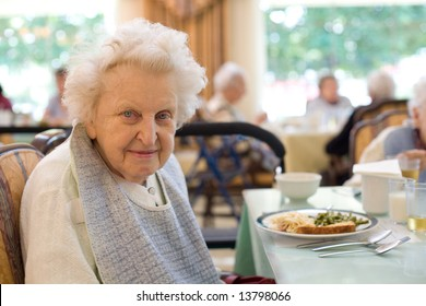 An smiling elderly woman sits down to enjoy a meal at her nursing home care center with a sunny background.