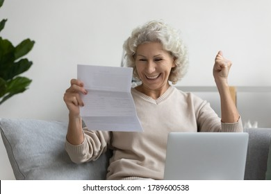 Smiling elderly woman sitting on couch in living room reading great news in postal paper correspondence letter from bank feels overjoyed very happy by free of financial obligations, paid debt concept