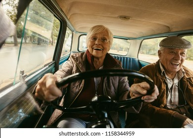 Smiling elderly woman in warm clothing driving car with husband sitting in passenger seat. Old couple having a great time on their drive.