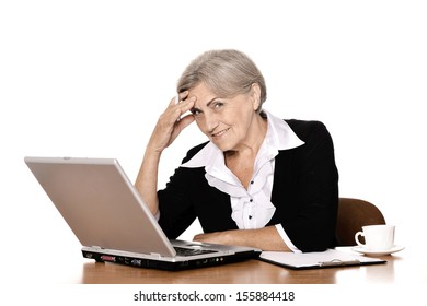 Smiling elderly woman working with laptop on white background