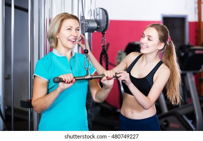 Smiling elderly and young women doing powerlifting on machines in jym