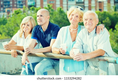 Smiling eldery people talking and drink at a plastic cup at the outdoor