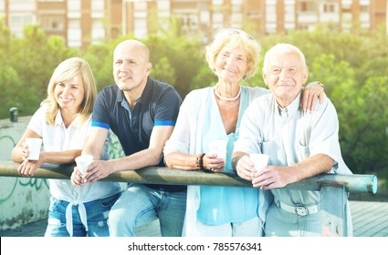 Smiling eldery people talking and drink at a plastic cup at an outdoor