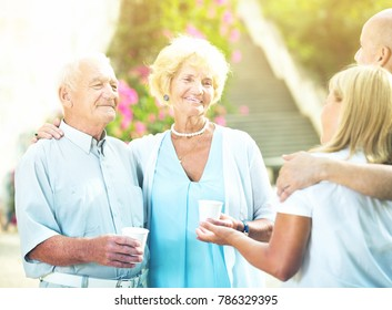 Smiling eldery people talking and drink at a plastic cup in an outdoor