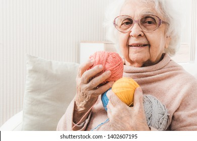 Smiling eldery woman holding colorful laces balls for knitting