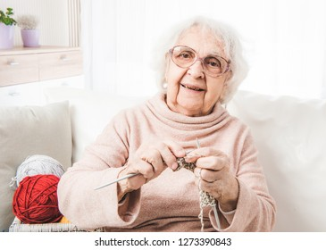 Smiling eldery woman knitting with colorful laces balls