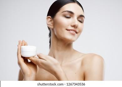 Smiling elegant brunette holding a skin cream