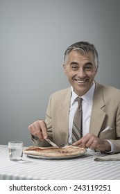 Smiling elegant businessman having a pizza during his lunch break