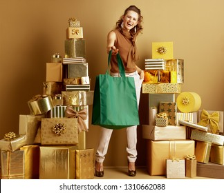 Smiling elegant fashion-monger in gold beige pants and brown blouse among 2 piles of golden gifts in front of plain wall giving eco friendly green bag. Modern shoppers choosing eco friendly products.