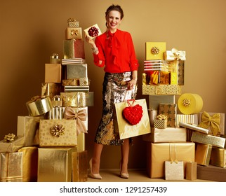 Smiling elegant fashion-monger in red blouse and golden sparkly sequin pencil skirt with shopping bag and red heart showing gift card or Valentine's Day greeting cards among 2 piles of golden gifts.