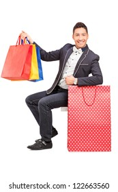 A smiling elegant guy posing with shopping bags in his hand isolated on white background