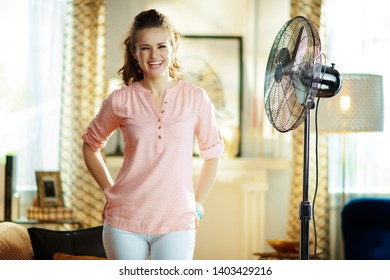 smiling elegant housewife at modern home in sunny hot summer day enjoying freshness in the front of fan.