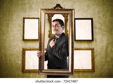 Smiling elegant man holding a frame with empty frames on the background