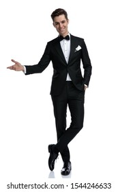 smiling elegant man in tuxedo inviting and presenting to side, standing isolated on white background, full body