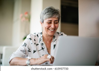 Smiling elegant mature woman sitting at table and using laptop.