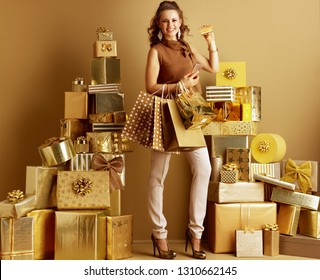 Smiling Elegant Shopper Woman In Gold Beige Pants And Brown Blouse With Shopping Bags Smartphone