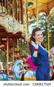 smiling elegant tourist woman in blue jeans overall riding on the carousel and waving.