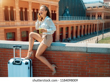 smiling elegant tourist woman with green smoothie and trolley bag speaking on a cell phone against Puerta De Atocha train station building