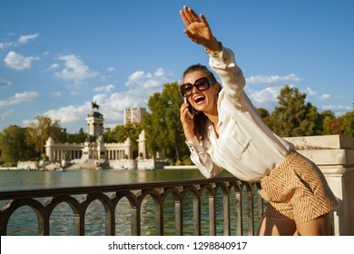 smiling elegant traveller woman in white blouse and shorts at El Retiro Park in Madrid, Spain using a smartphone and waving to someone or local young party woman meets with friends to go hang out.