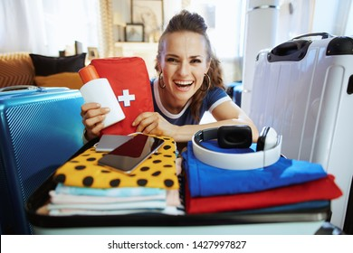 smiling elegant woman in blue t-shirt with spf and first aid kit getting prepared for travel in the modern house in sunny summer day.