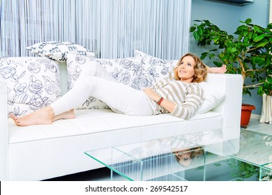 Smiling elegant woman lying on a sofa in a living room. Home interior, furniture. Lifestyle.