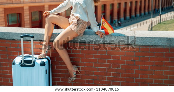 smiling elegant woman with Spain flag and trolley bag sitting on parapet in the front of Puerta de Atocha