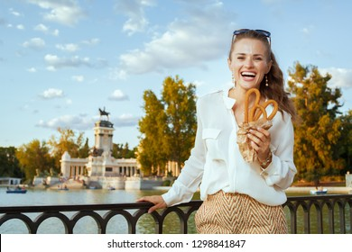 smiling elegant woman in white blouse and shorts with traditional Spain churro at Buen Retiro Park in Madrid, Spain. churros - classic Spanish sweet treat. blue sky. Sunny summer evening.solo traveler