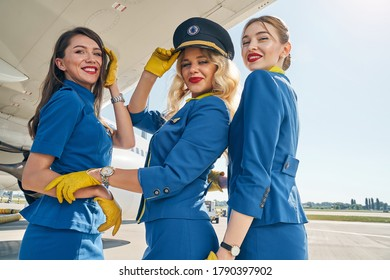Smiling elegant young stewardess in a pilot cap and her colleagues in uniforms looking ahead