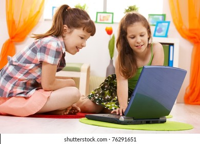 Smiling elementary age schoolchildren browsing internet on laptop computer at home.?
