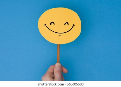Smiling emoji. Male hand holding a yellow emotion face with a hand drawn expression