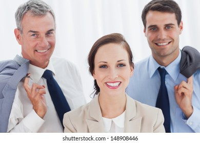 Smiling employee posing with her work team in bright office