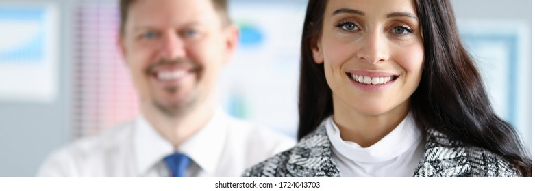 Smiling employees man and woman stand in office. Creating favorable psychological climate in team. Strict control when performing certain tasks. Employees feel safe and confident in future