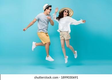 Lächelnde asiatische Paare Touristen im Sommer Strand lockere Kleidung springen einzeln auf hellblauem Studiohintergrund