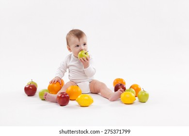 smiling energetic baby on a white background fruits among encourages a healthy lifestyle. The picture with depth of field