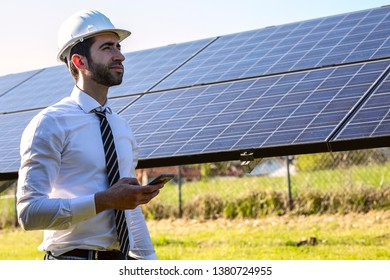 Smiling engineer in front of solar panels with smartphone