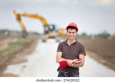 Smiling engineer with helmet standing in front of excavator on road construction site