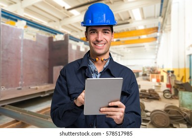 Smiling engineer using a tablet in a facility
