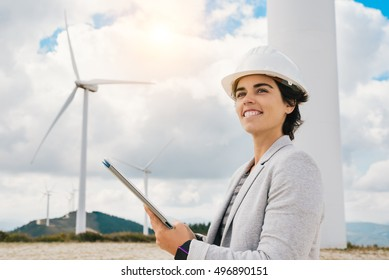 Smiling engineer woman holding tablet with safety helmet at wind turbine farm in eolic park generating energy with air flow with spinning blades. Clean renewable green wind power concept.